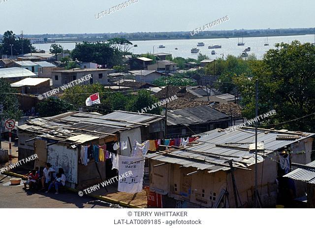 Shanty town,cardboard houses. Women seated. Washing lines. Sea. Pleasure boats moored