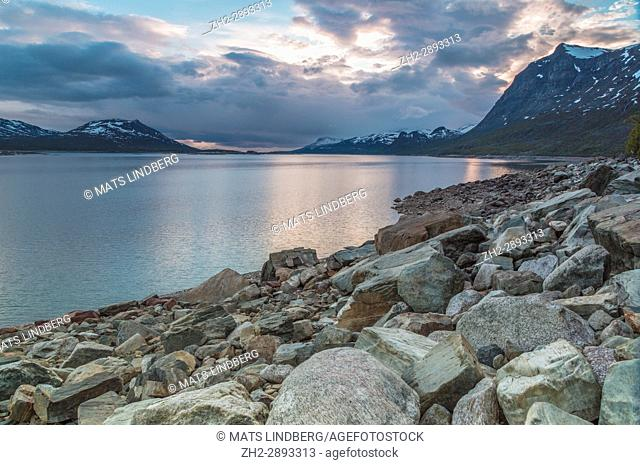 Sun reflecting in water, mountains with snow in background and a rocky beach in foreground, Stora sjöfallets national park, Gällivare, Swedish Lapland, Sweden