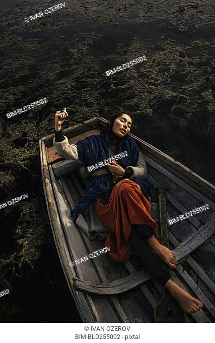Location woman wearing traditional clothing laying in rowboat
