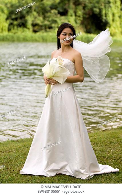 A beautiful asian woman in her wedding dress stands near a lake, the veil flying in the wind