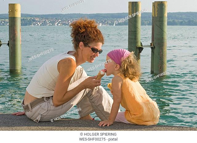 Germany, Baden-Württemberg, Lake Constance, Mothee an daughter 4-5 eating ice cream