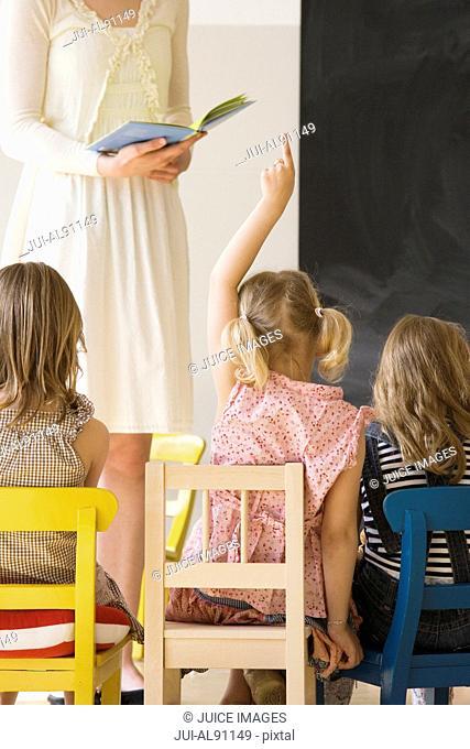 Girl raising hand while preschool teacher reads