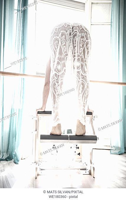 Woman Exercising on Pilates Machine With Sunlight in Switzerland