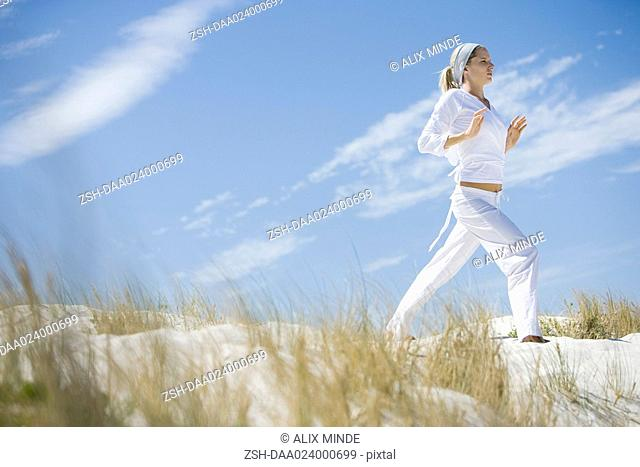 Young woman standing on dune, exercising