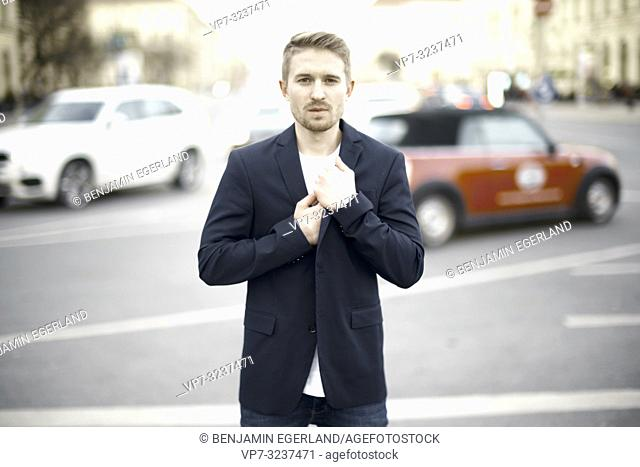 young man at street in city, wearing business blazer, in Munich, Germany