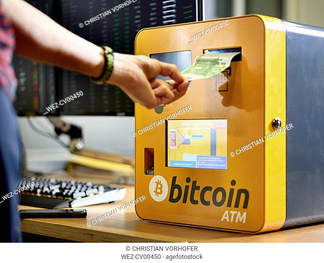Hand inserting 100 Euro note into bitcoin ATM
