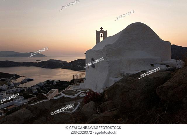 White chapel at sunset In Hora and view to the Ormos Harbour on Ios Island, Cyclades Islands, Greek Islands, Greece, Europe
