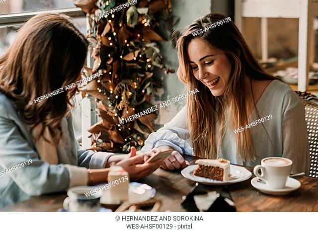 Two happy young women with cell phone meeting in a cafe
