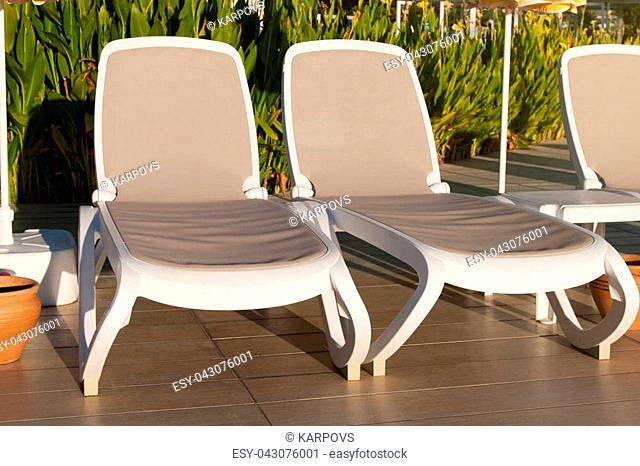 two beige plastic loungers in front of the pool