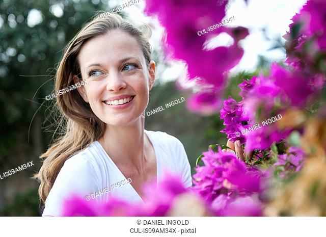 Portrait of mid adult woman next to purple blossom, Sardinia, Italy
