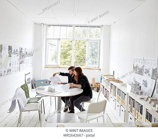 A modern office. Two people at a meeting discussing plans. Architectural drawings and building models