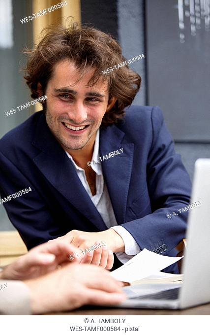 Smiling young businessman talking at sidewalk cafe