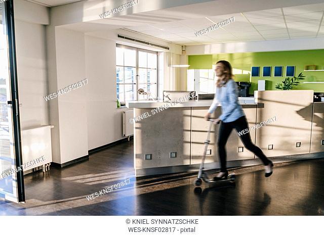 Businesswoman using kickboard in office