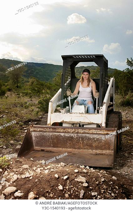 Female construction worker operating wheel loader
