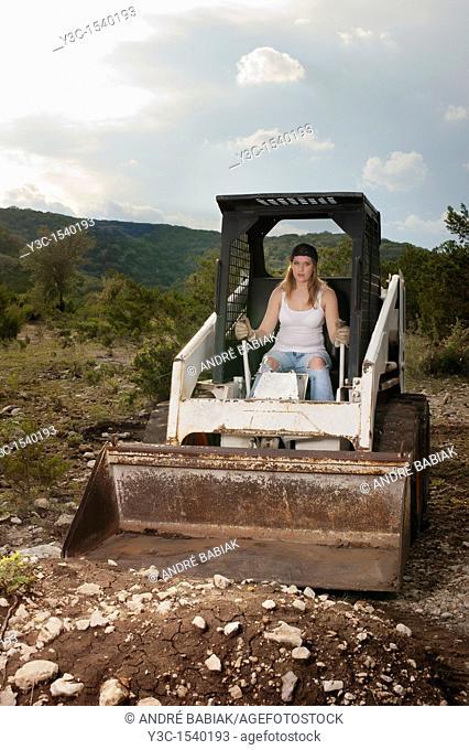 Female construction worker operating wheel loader