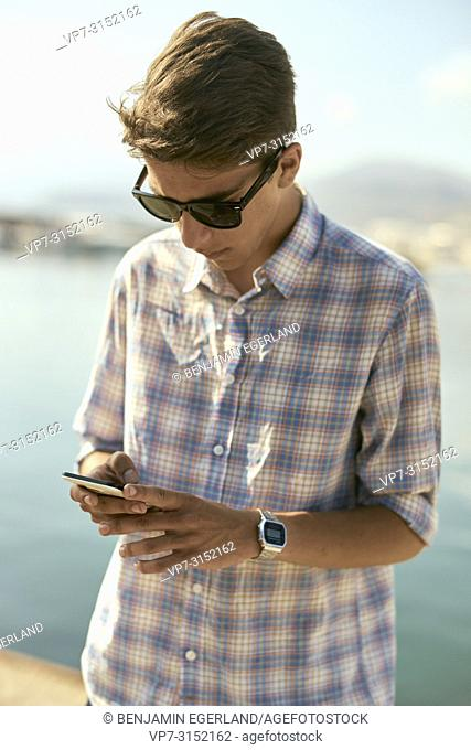 young man using smartphone at seaside in Chersonissos, Crete, Greece, wearing smartwatch on wrist