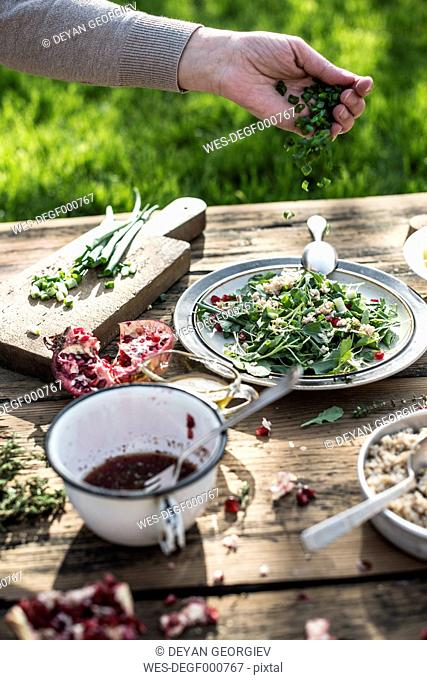 Preparing green salad with pomegranate, manna croup and spring onion, pomegranate dressing
