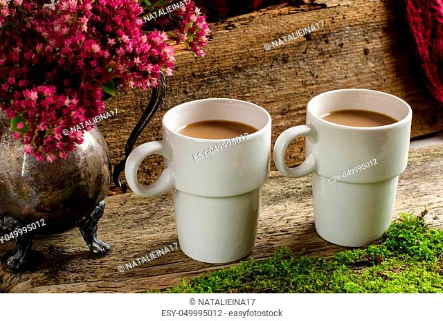 Two cups of coffee in white cups. Autumn flowers in a silver jug. Background - old Board. Vintage style