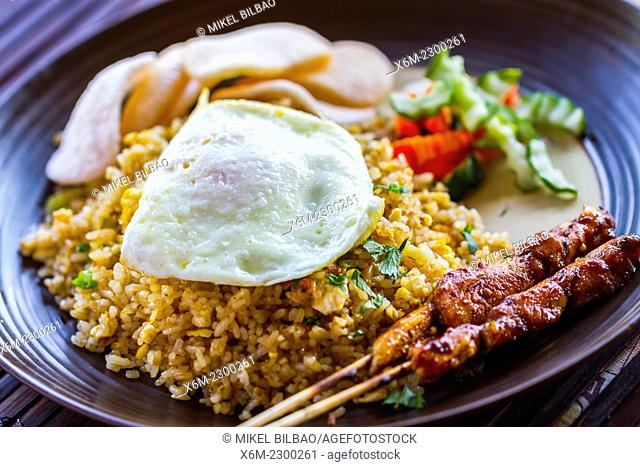 Nasi goreng (Indonesian traditional recipe with fried rice, fried egg, prawn crackers and meat on steaks or sates)