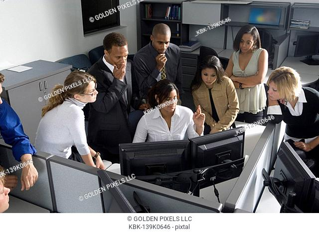 Group of young workers in office gathered around computer screen