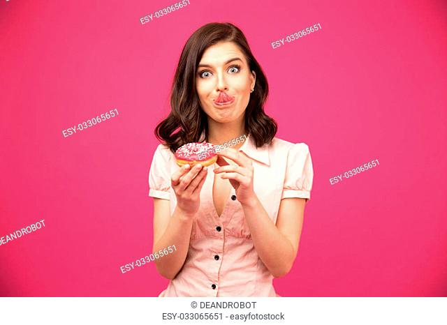 Young woman holding donut and showing her tongue over pink background. Looking at camera