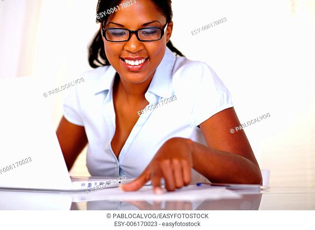 Afro-american with black glasses studying with laptop and documents