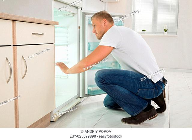 Young Man Crouching On Floor And Looking Into An Empty Refrigerator In Kitchen