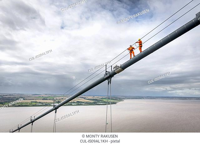 Bridge workers working on cable of suspension bridge. The Humber Bridge, UK was built in 1981 and at the time was the world's largest single-span suspension...