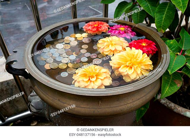 A small floral wishing well with coins on Penang Hill, Malaysia