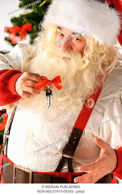 Santa Claus holding keys with red ribbon standing near Christmas Tree. New year - new home concept