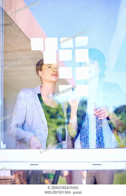 Two female creative professionals with adhesive notes behind windowpane