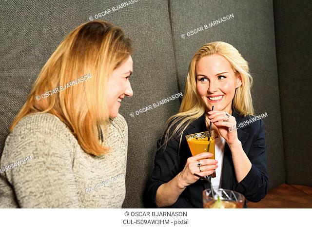 Mid adult women in public house holding cocktails face to face smiling