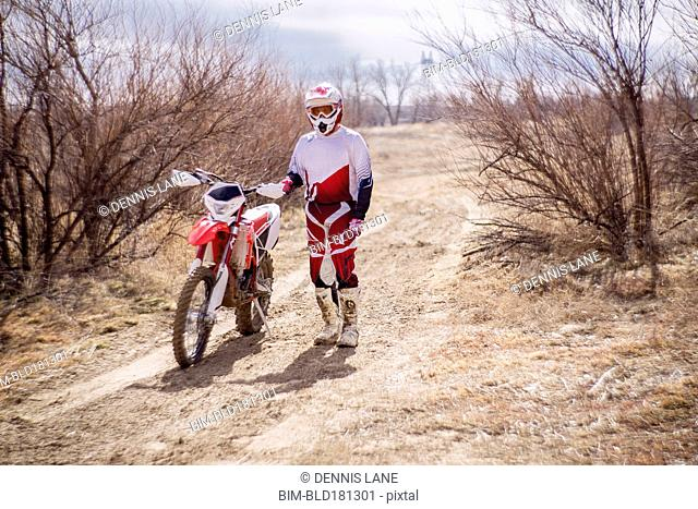 Dirt bike rider standing with motorcycle in rural field
