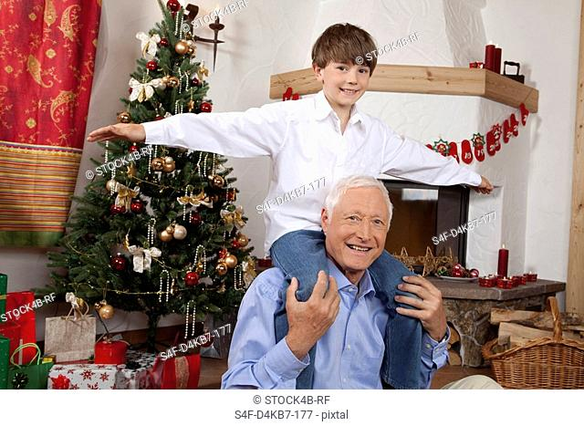 Grandfather carrying boy on shoulders at Christmas tree