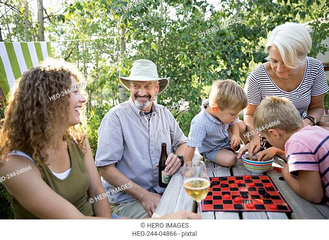 Multi-generation family drinking at campsite picnic table