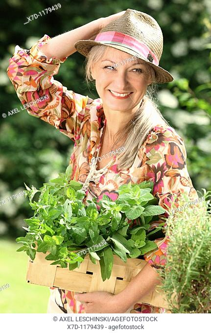 older woman picking fresh herb