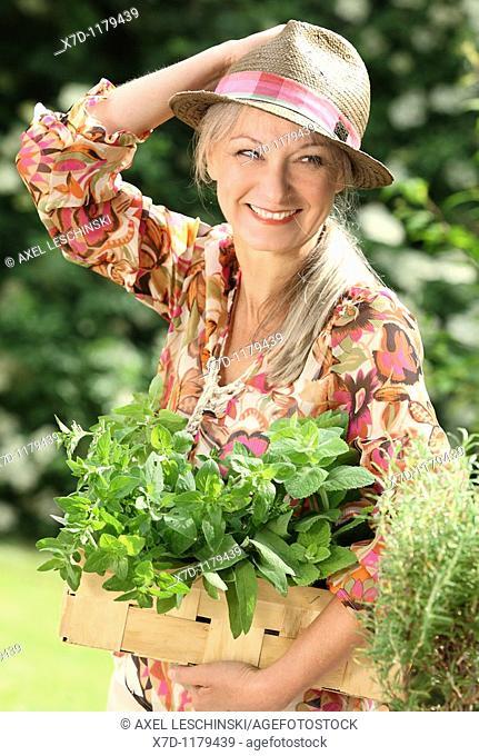 older woman picking fresh herb