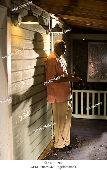 Portrait of African American man standing on porch of house at night