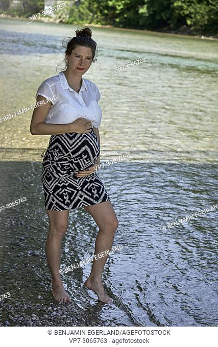 Pregnant woman standing in river Isar. Munich, Germany