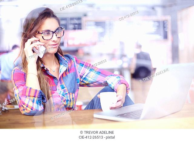 Woman using laptop and talking on cell phone at cafe