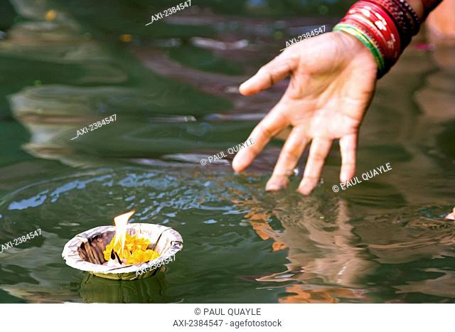 Hindu woman immersed in the holy Ganges water, casting off a container with a flame as a religious offering; Uttar Pradesh State, India