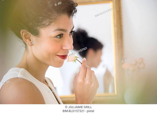 Mixed race woman smelling flower near mirror