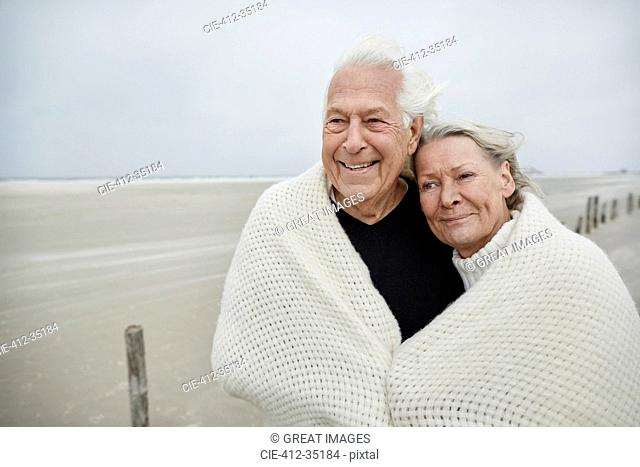 Smiling affectionate senior couple wrapped in a blanket on beach