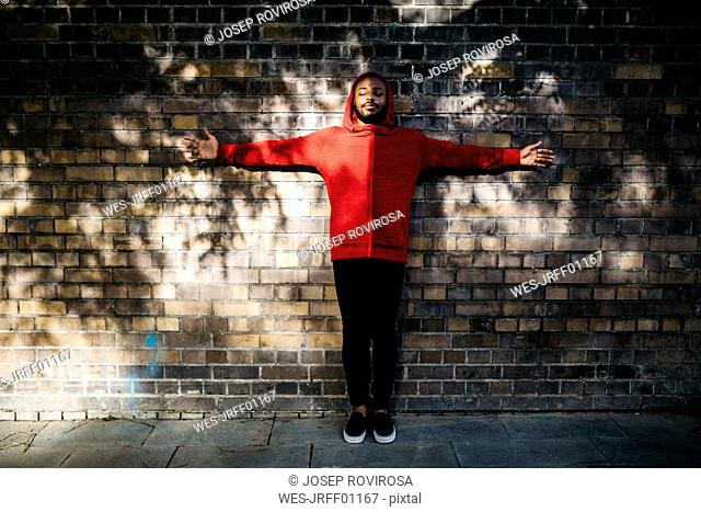 Young man wearing red hoodie standing at a wall with outstretched arms