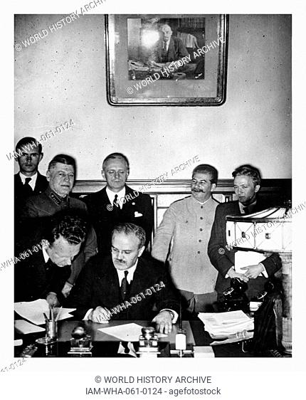 Russian Foreign Minister Vyacheslav Molotov signing the German-Soviet non-aggression pact, Moscow, Russia, 1939. German Minister Von Ribbentrop and Josef Stalin...
