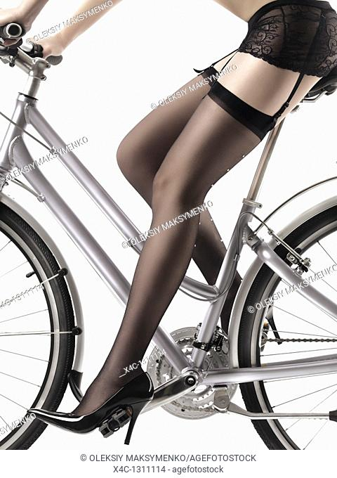 Closeup of legs of a sexy woman wearing stockings and high heel shoes riding a bicycle