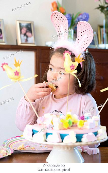 Young girl wearing bunny ears, eating cake