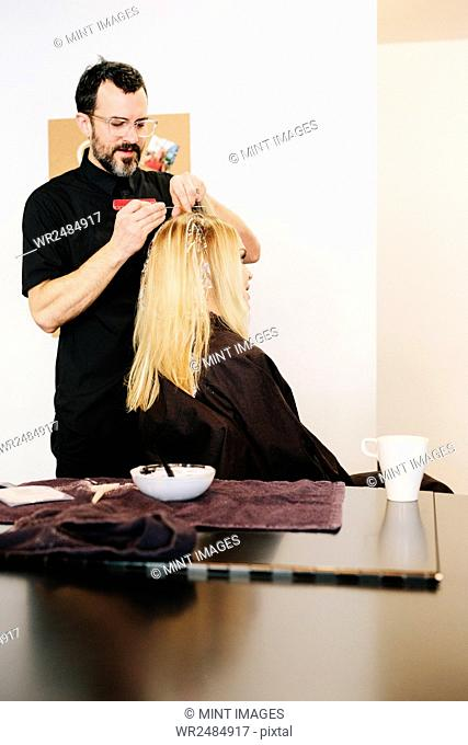 A hair colourist working with foils to give a client with long blonde hair highlights and lowlights using colour