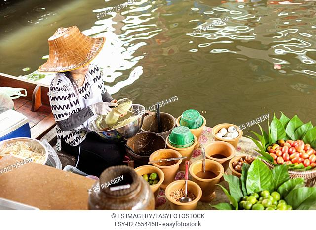 A woman in a floating kitchen vegetables in Taling Chan Floating Market, Bangkok, Thailand