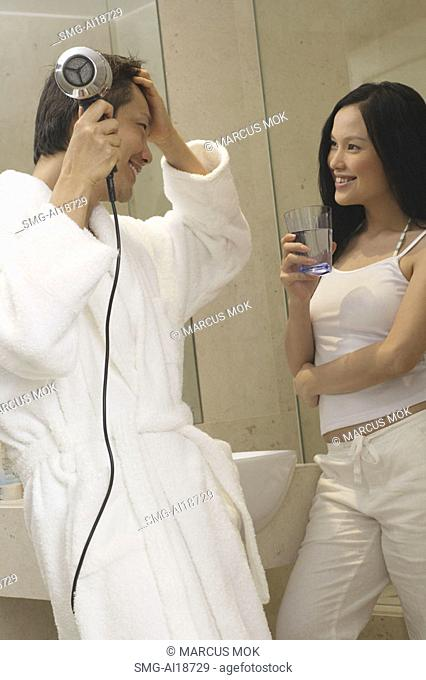 Couple in bathroom, man in robe using hairdryer, woman standing with glass of water